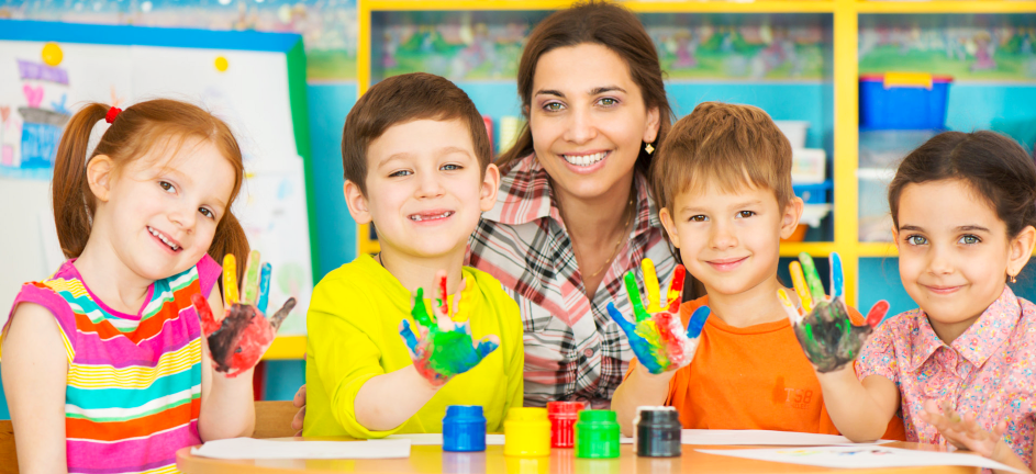 4 children having a paint in their hand and a teacher